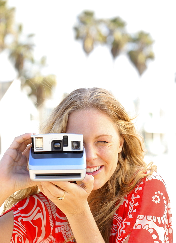 Woman taking photograph with instant camera