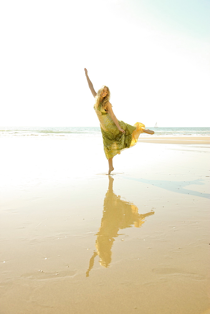 Woman standing on one foot at beach