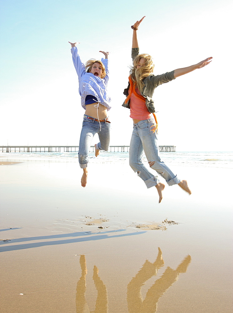 Two women jumping on beach