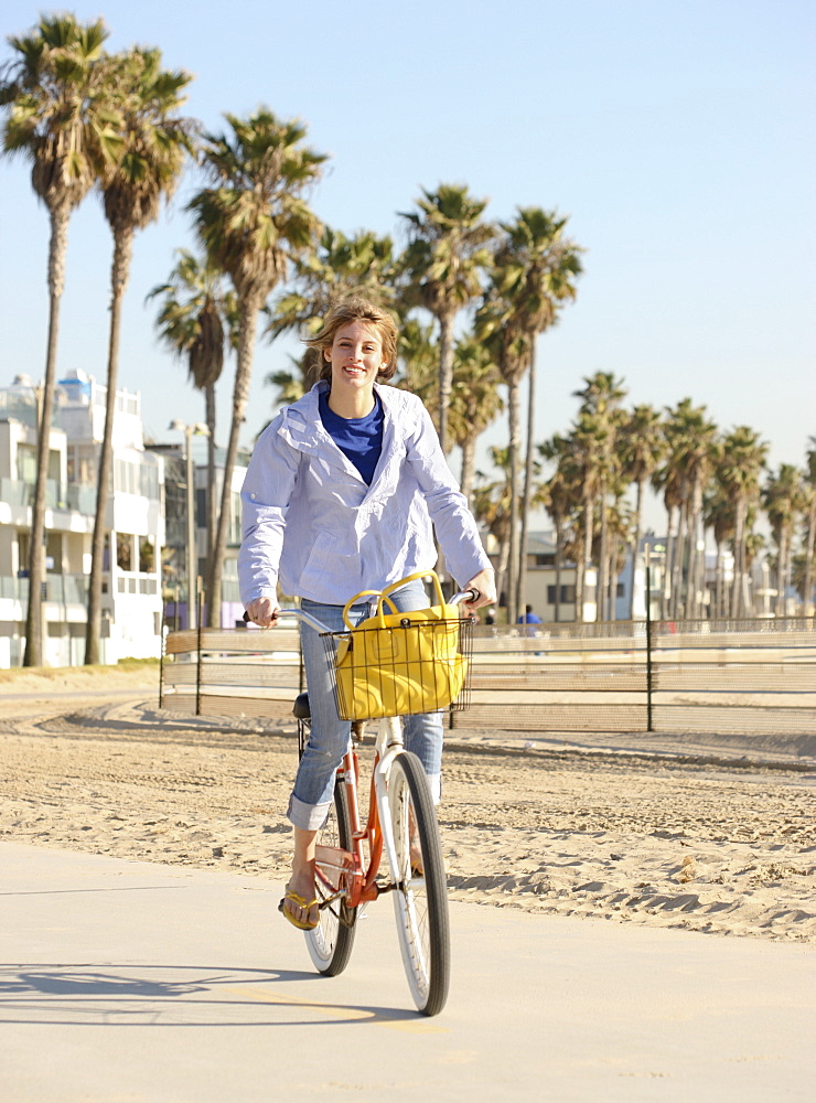 Woman riding bicycle at beach