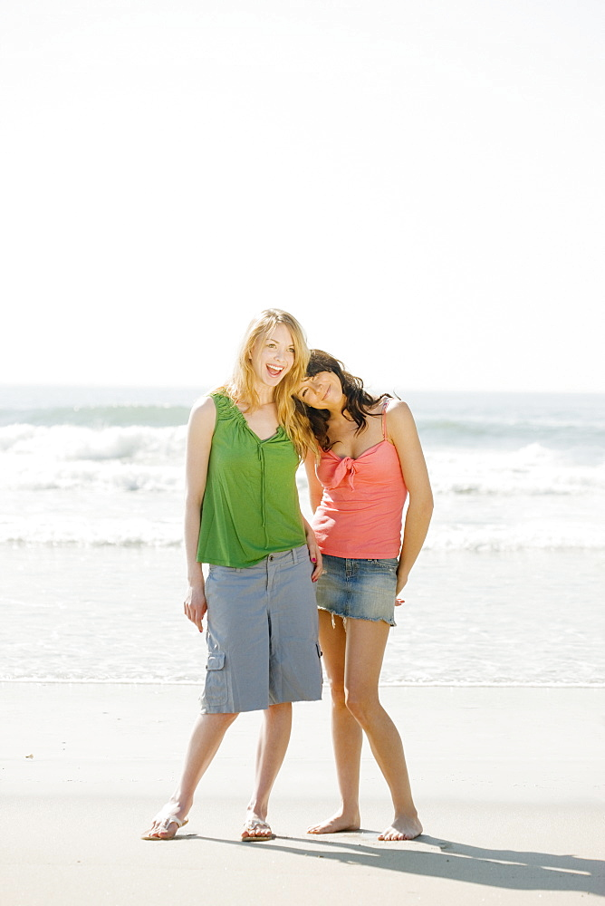 Two women standing on beach