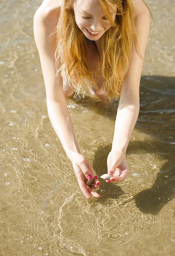 Woman picking up seashells at beach
