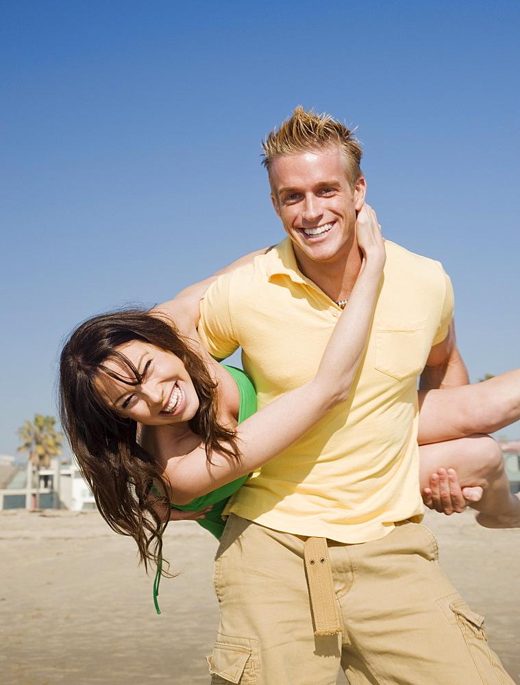 Man holding girlfriend behind back