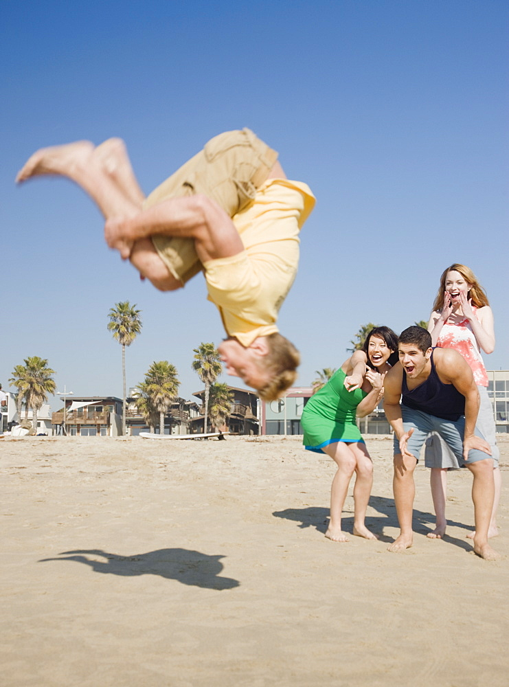 Man doing back flip on beach