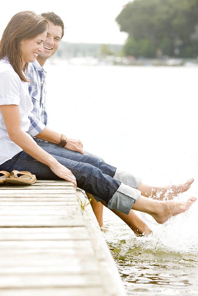 Couple sitting on dock and splashing feet in lake