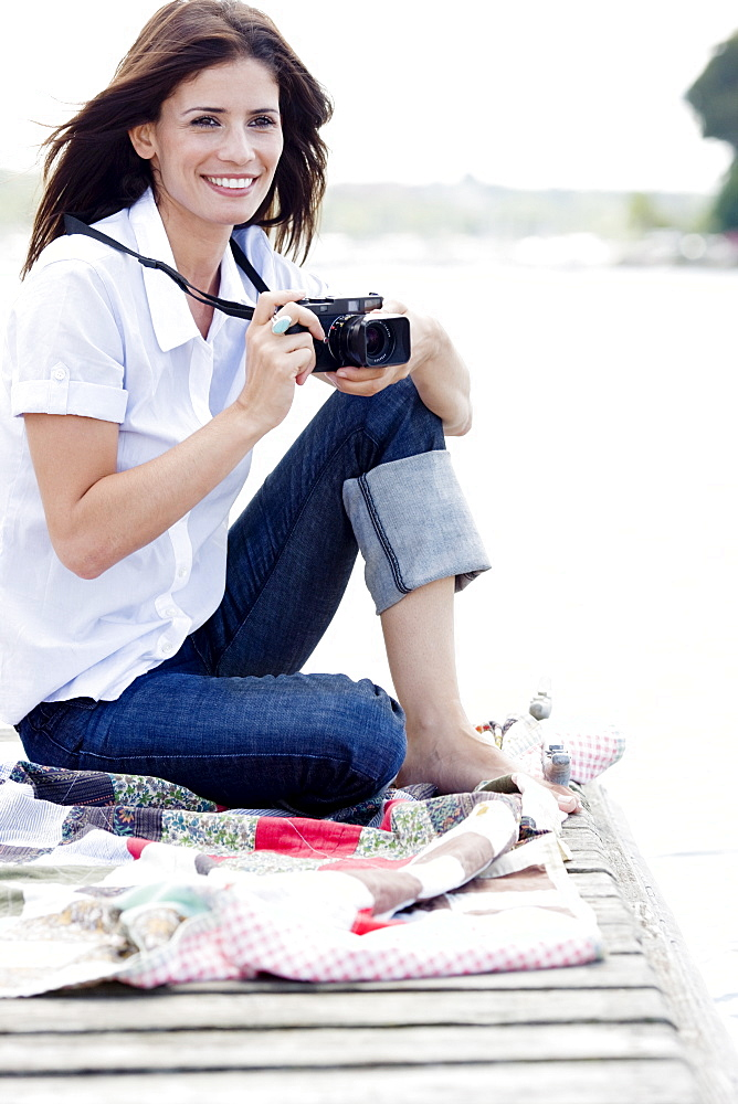 Woman with camera sitting on dock