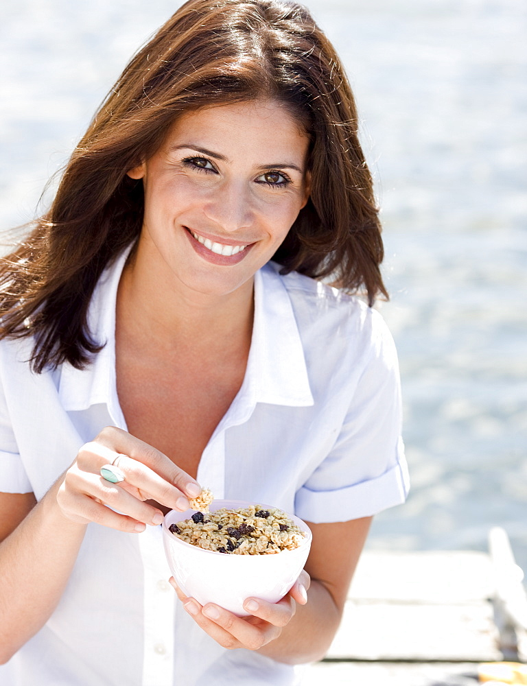 Portrait of woman eating granola on dock