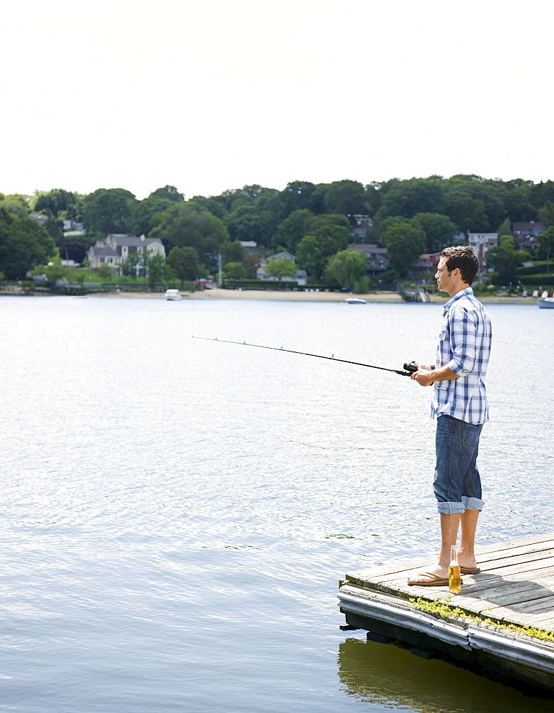 Man fishing off dock with beer at feet