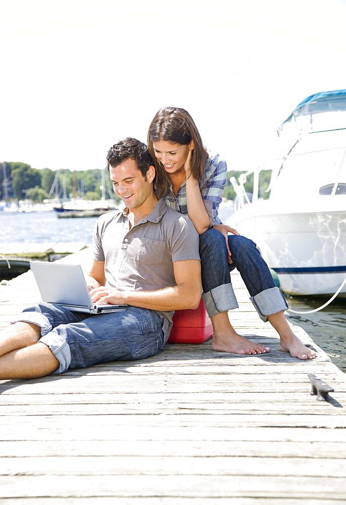 Couple using laptop on dock