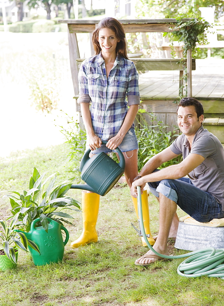 Couple watering plants in backyard