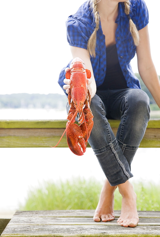 Portrait of woman holding lobster on deck