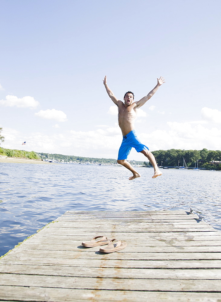 Portrait of man jumping off dock into lake
