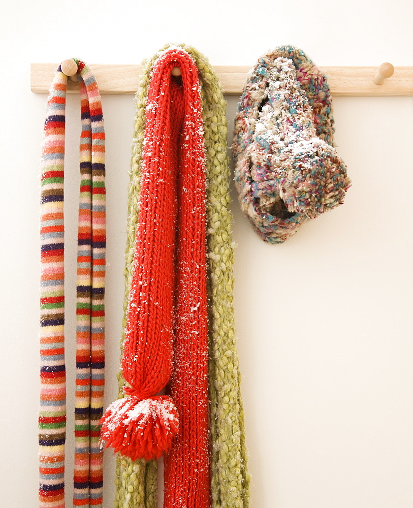 Snowy scarves hanging on rack