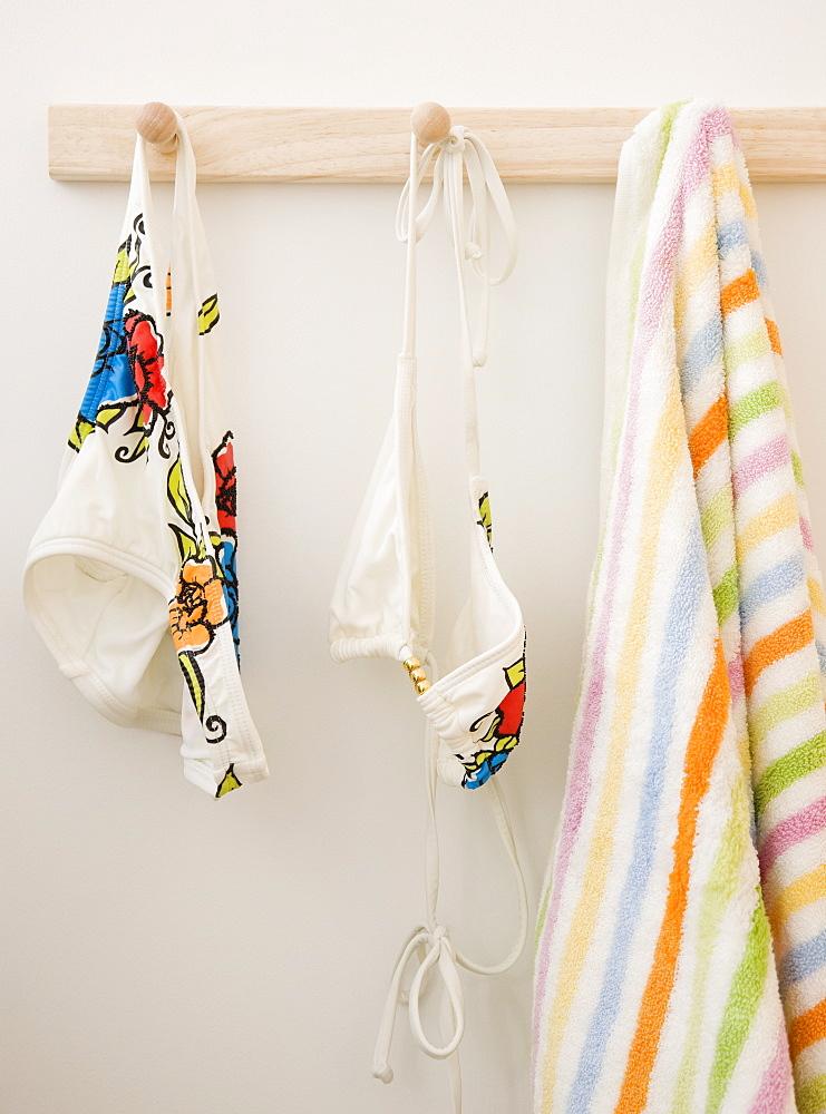 Bikini and towel hanging on rack