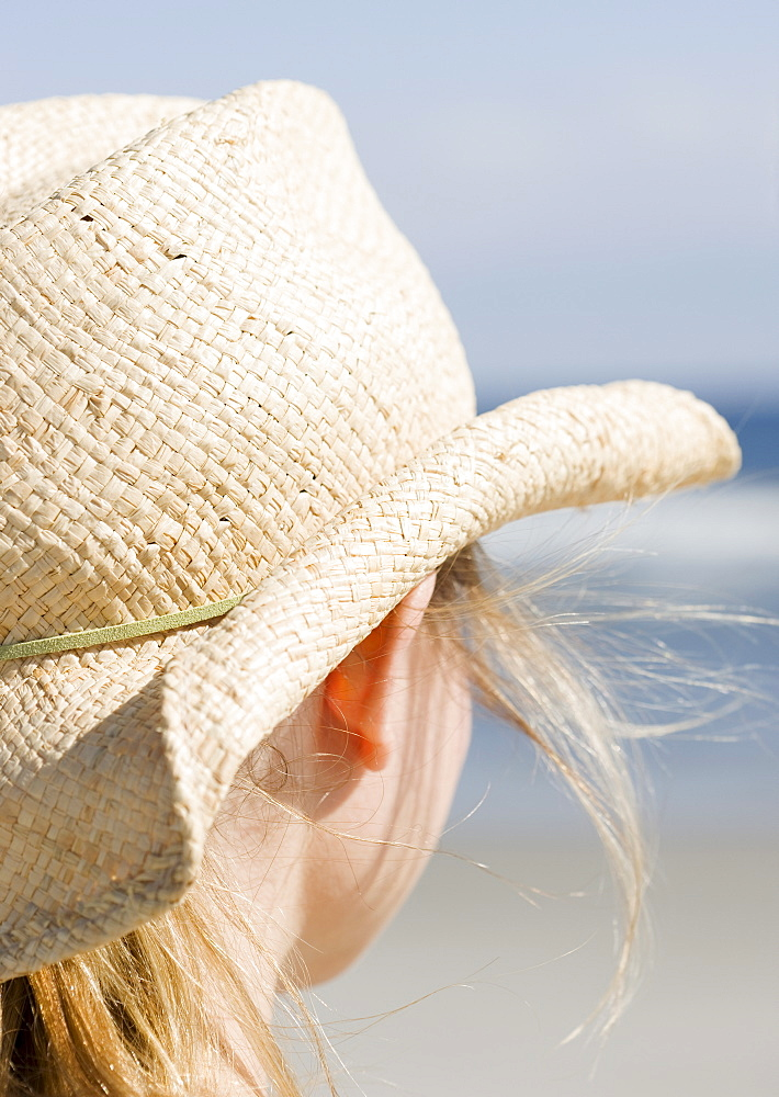 Woman in cowboy hat on beach
