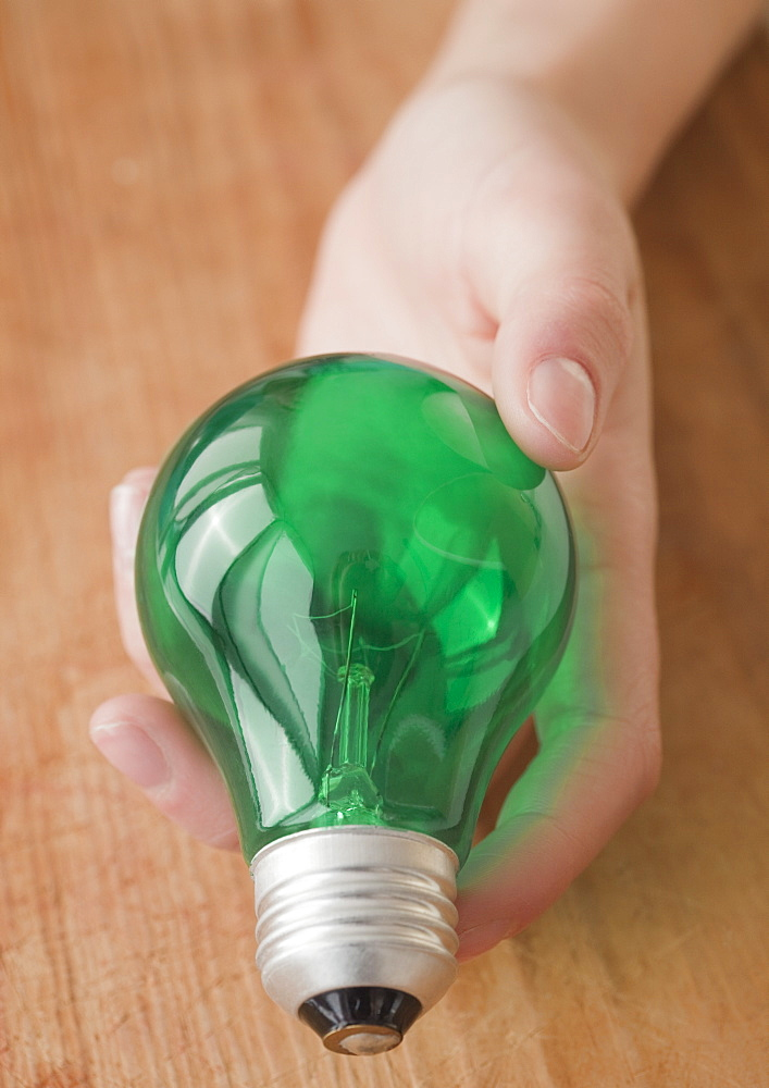 Woman holding green light bulb