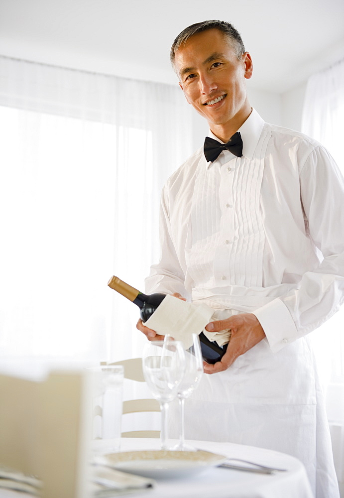 Smiling waiter holding champagne bottle and looking at camera