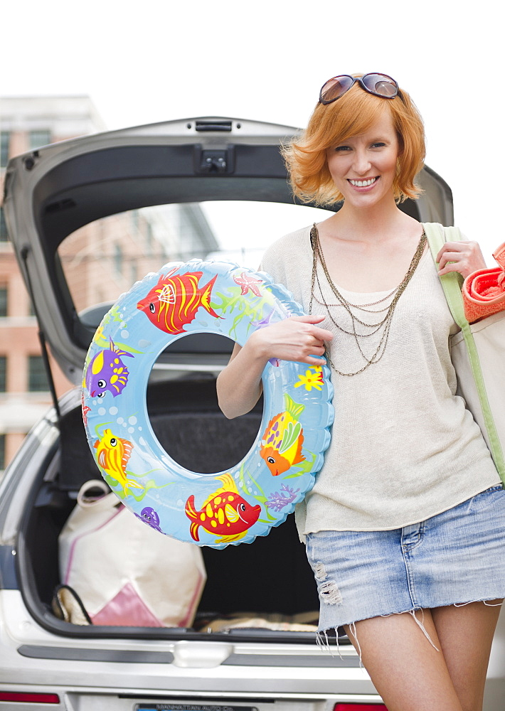 Portrait of young woman with beach gear in front of car