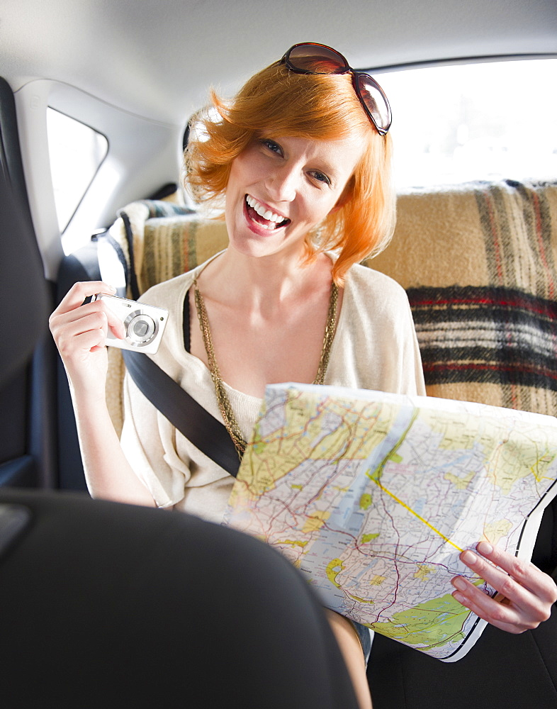 Portrait of young woman holding map in car
