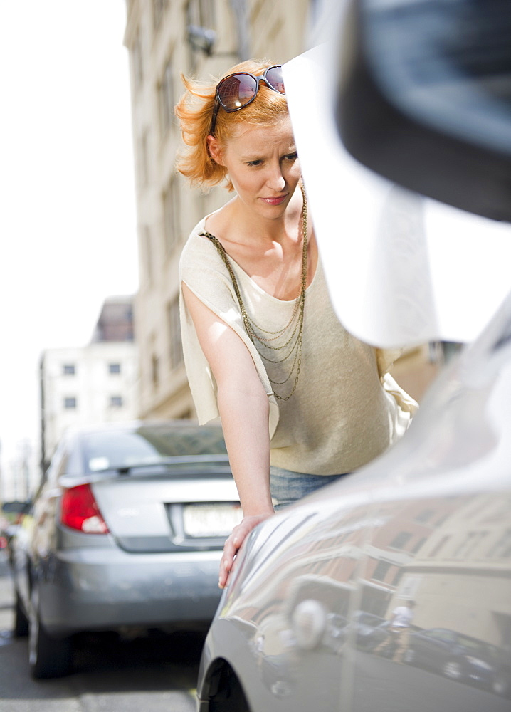 Woman looking at broken down car
