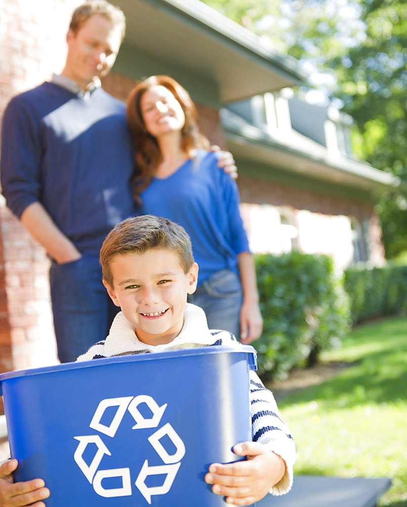 USA, New York, Flanders, Boy (8-9) holding bucket with recycling symbol, parents in background