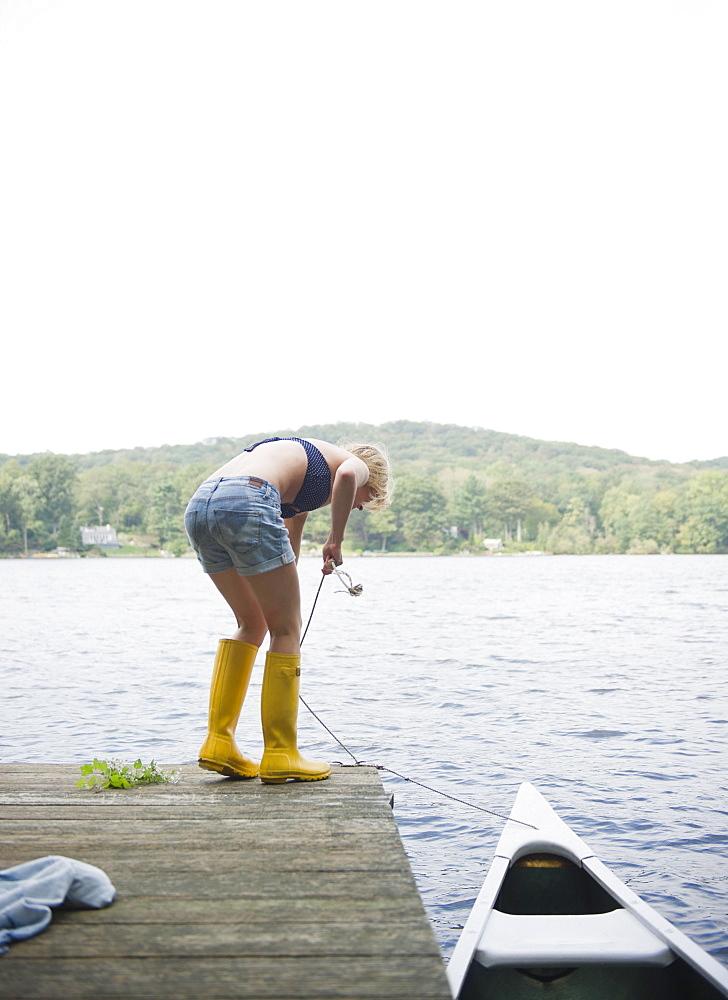 USA, New York, Putnam Valley, Roaring Brook Lake, Rear view of woman mooring boat