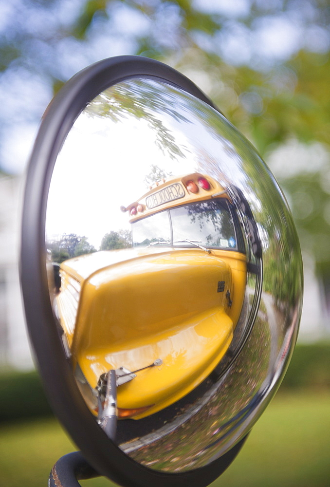 Reflection of school bus in rear view mirror