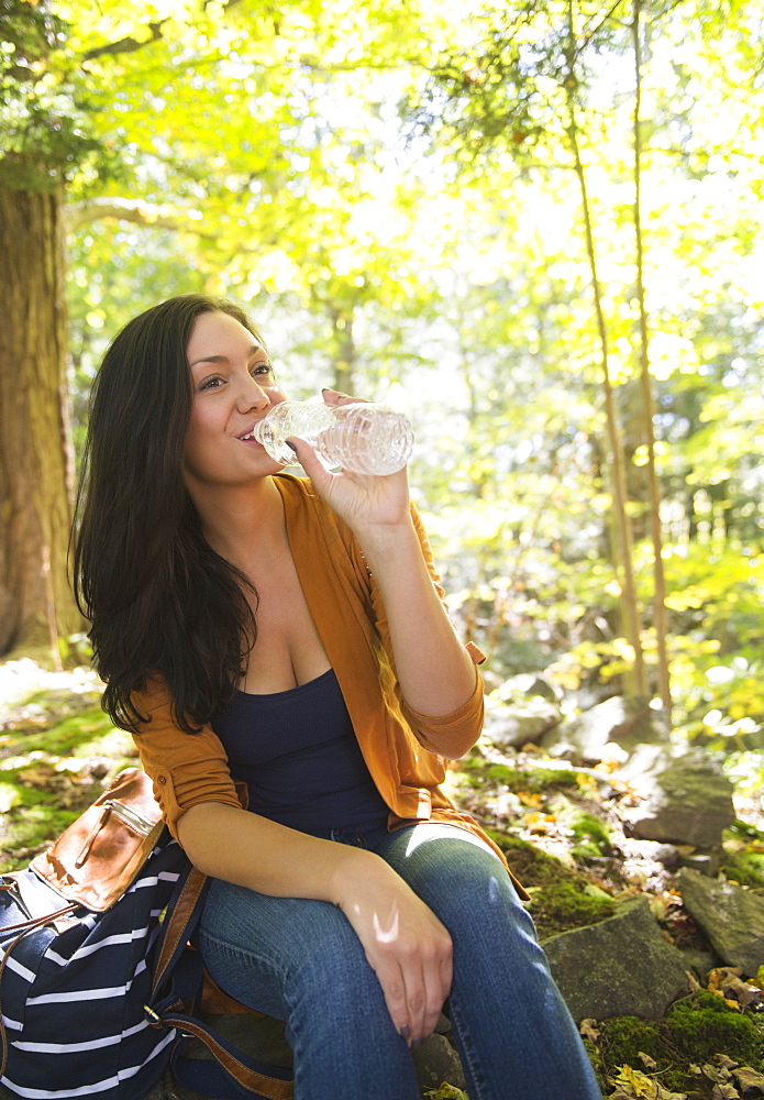 Woman drinking water in forest, Newtown, Connecticut