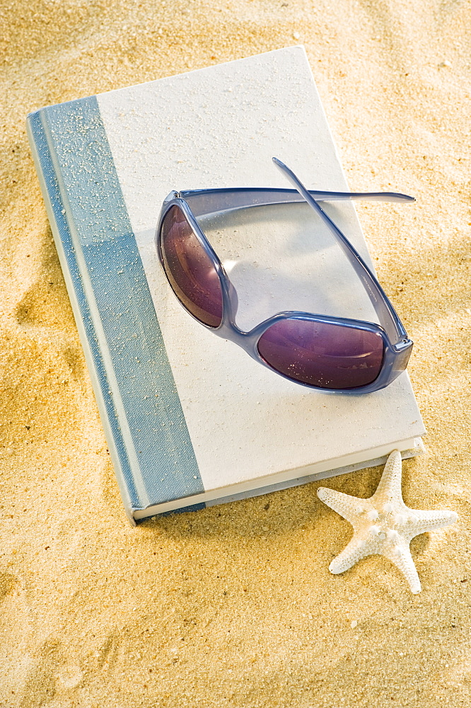 A book with sunglasses on sand