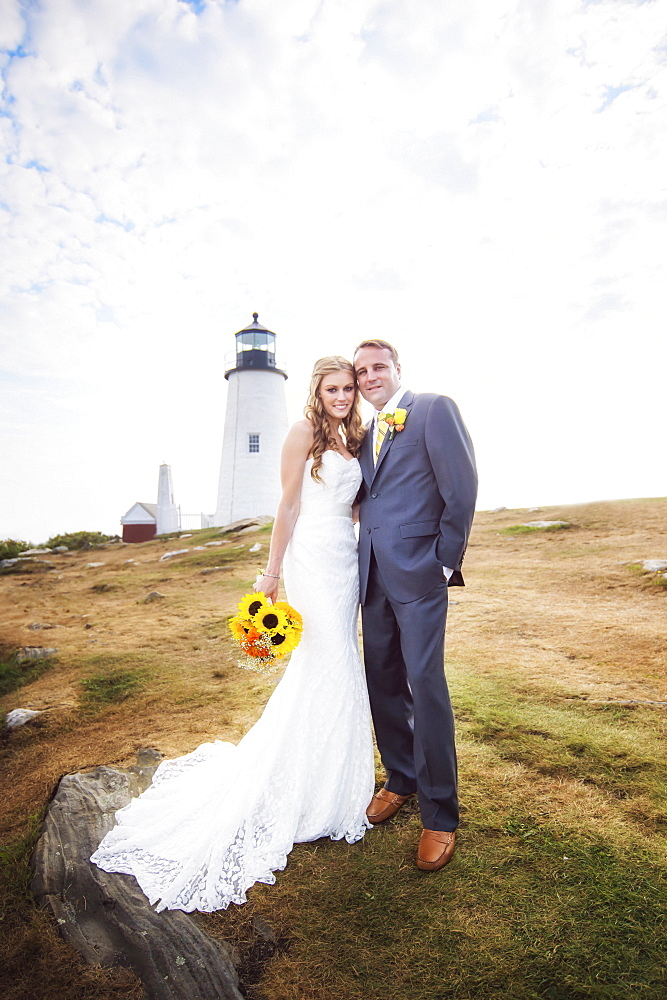 Portrait of married couple, lighthouse in background, USA, Maine, Bristol