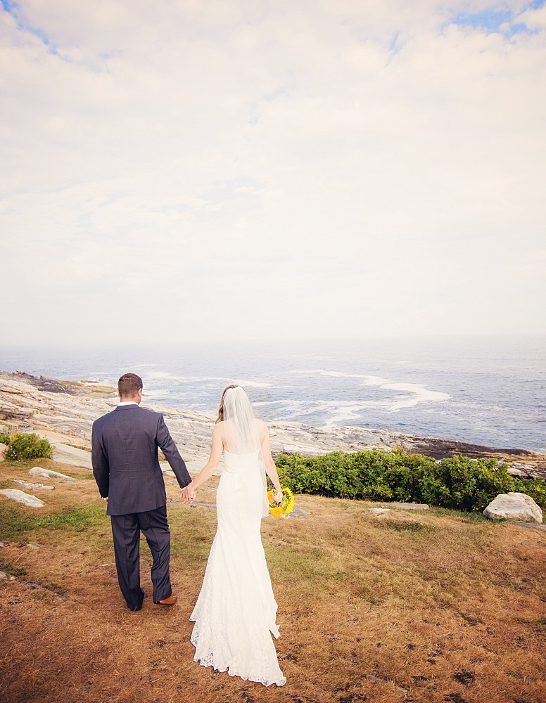 Rear view of married couple walking by sea, USA, Maine, Bristol