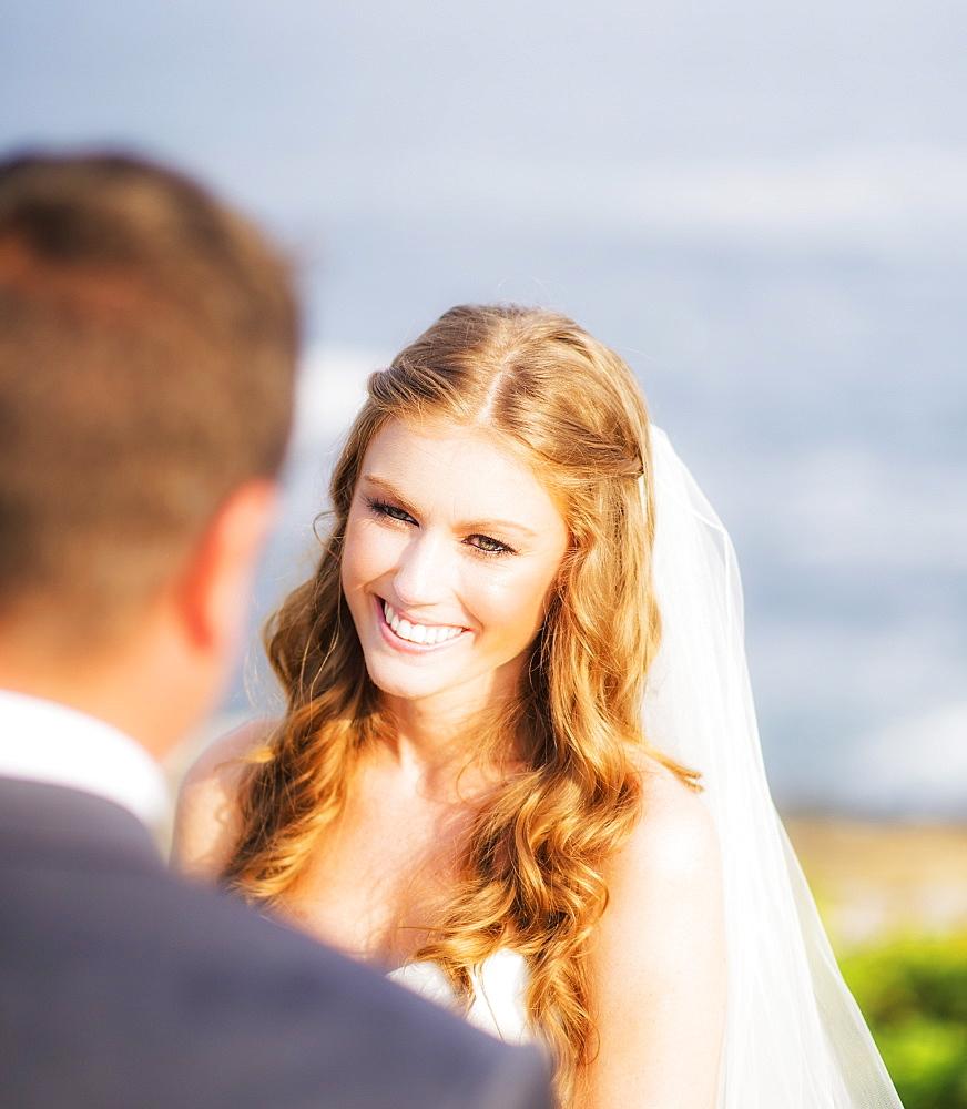 Groom looking at bride, sea in background