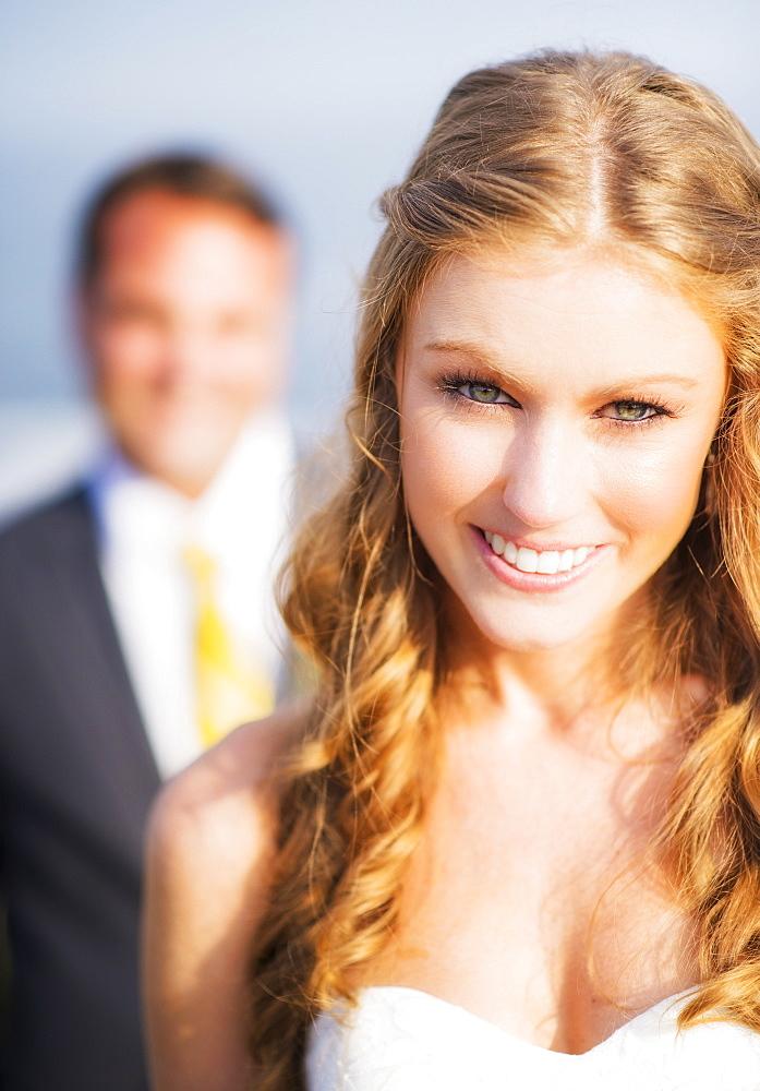 Portrait of smiling bride, groom in background