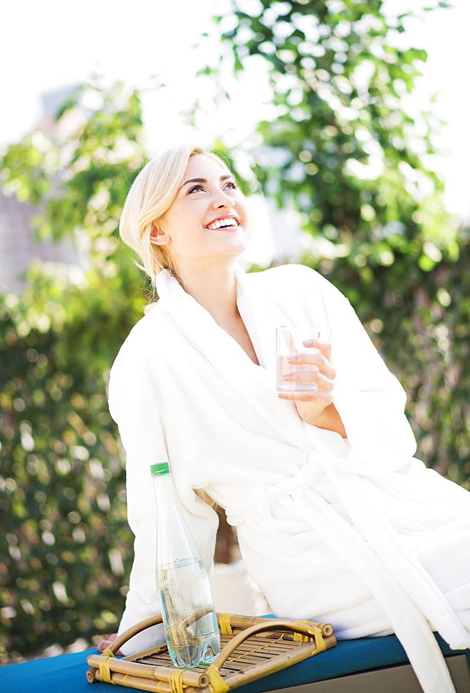 Teenage girl (16-17) wearing bathrobe sitting in garden