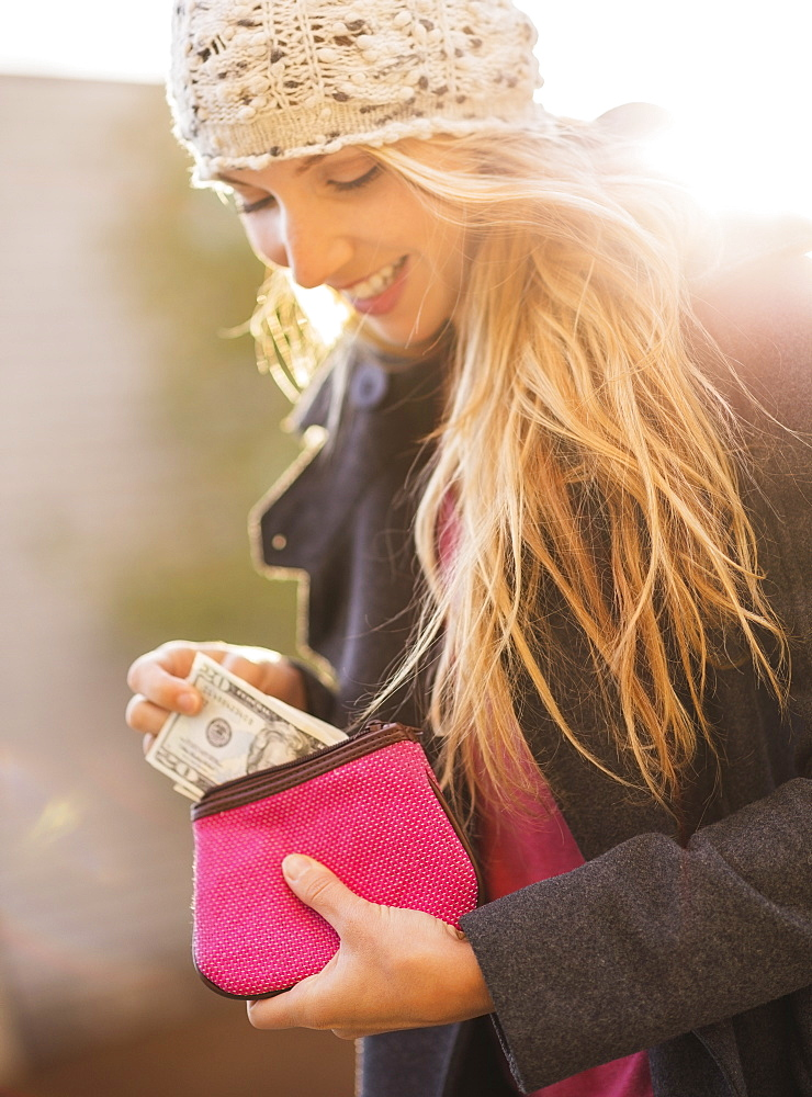Portrait of woman holding purse with banknotes, USA, New York City, Brooklyn, Williamsburg
