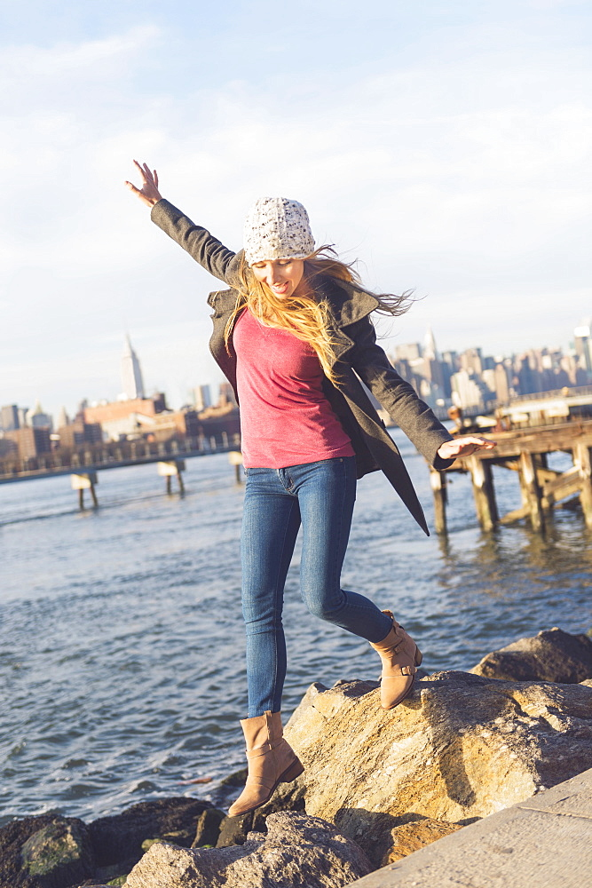 Blond woman stepping on stones by river, skyline in background, USA, New York City, Brooklyn, Williamsburg