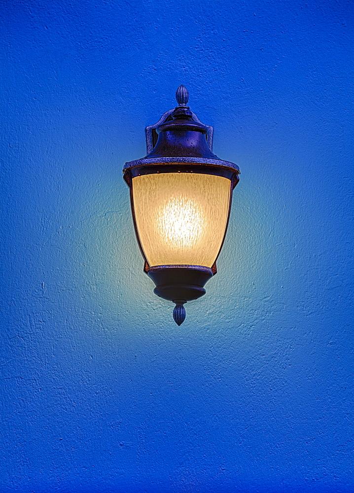 Illuminated antique street lantern floating over blue background