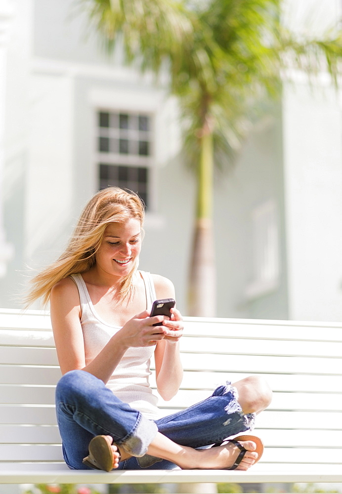 Young woman using mobile phone, Jupiter, Florida, USA