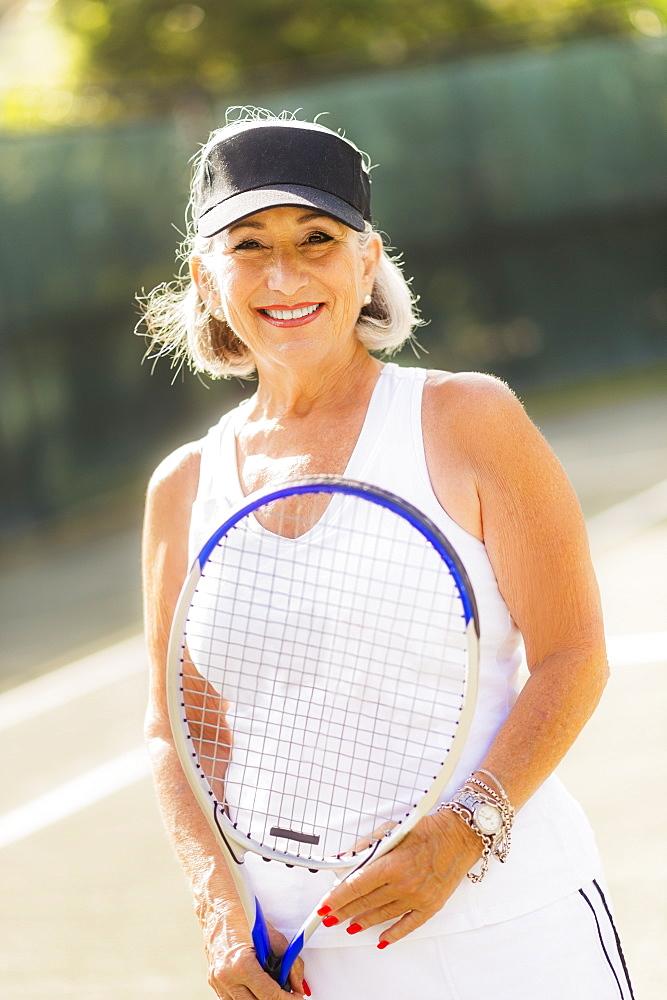 Portrait of senior woman on tennis court