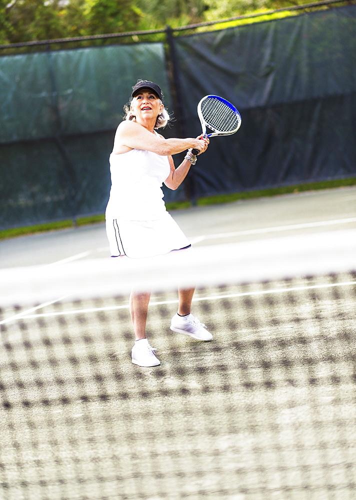 Senior woman playing tennis, Jupiter, Florida