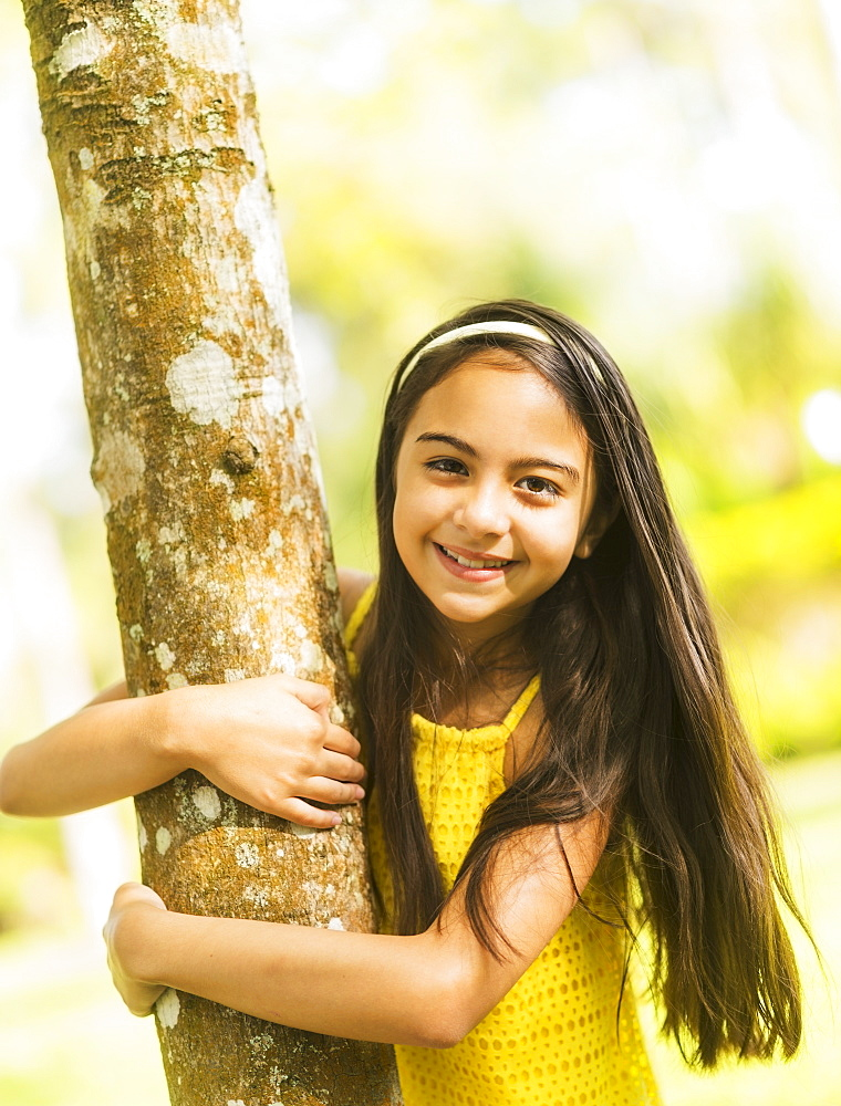 Portrait of girl ( 8-9) hugging tree trunk