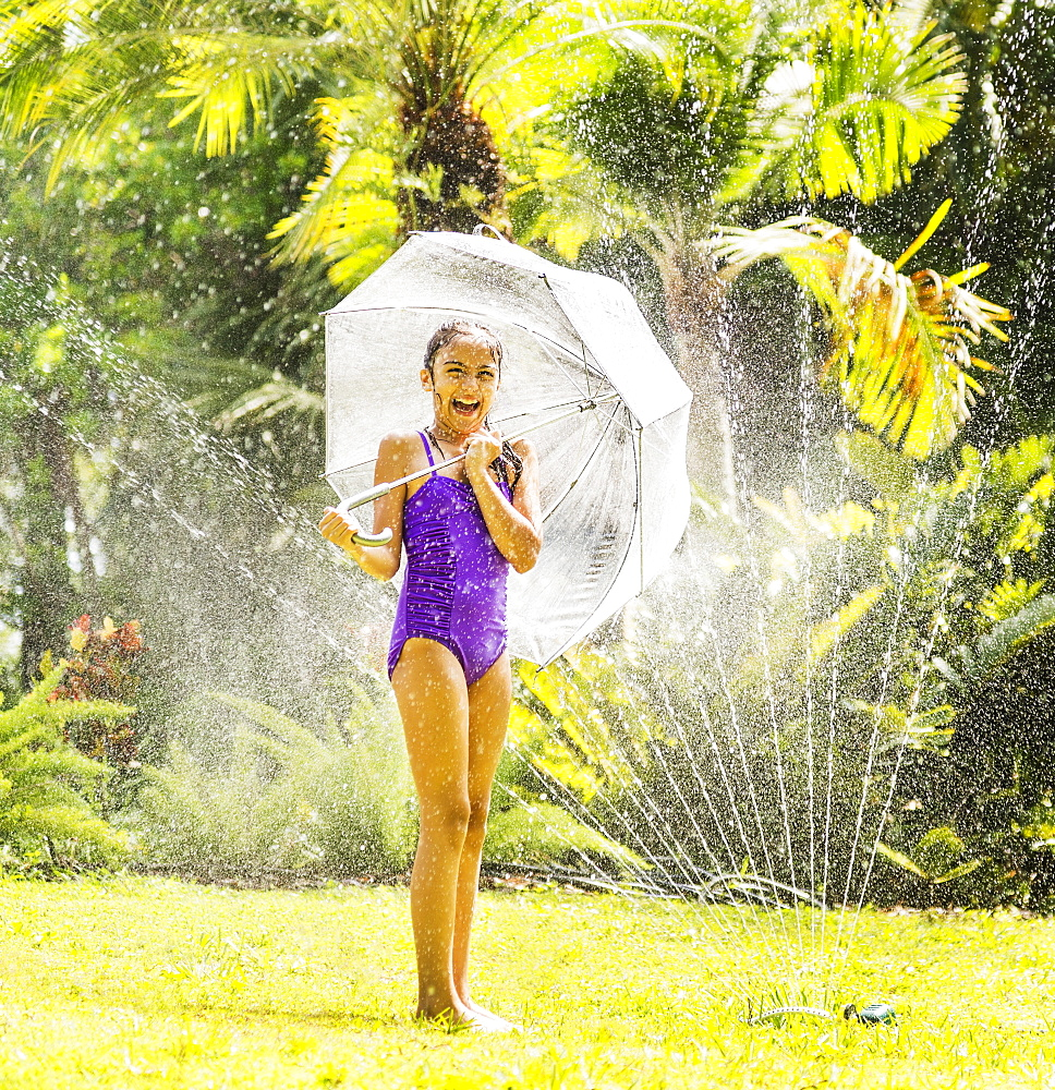 girl (8-9) playing in sprinkler