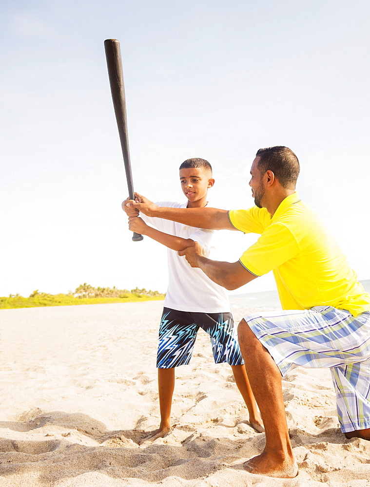 Father and son (10-11) playing baseball on beach, Jupiter, Florida