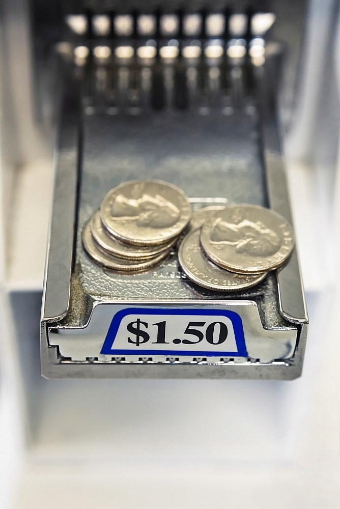 Quarters on sliding tray of coin operated washing machine