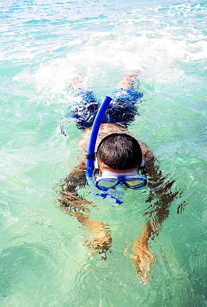 Boy (10-11) snorkeling in sea