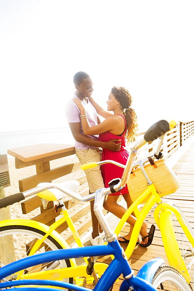 Young couple embracing on boardwalk, Jupiter, Florida