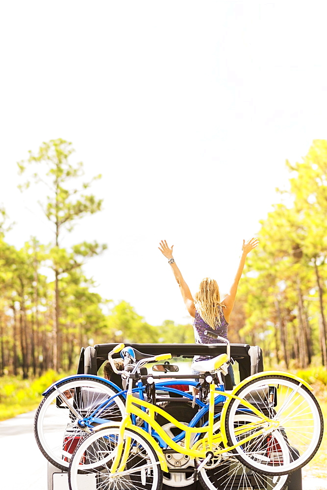 Woman rising hands in car, Tequesta, Florida