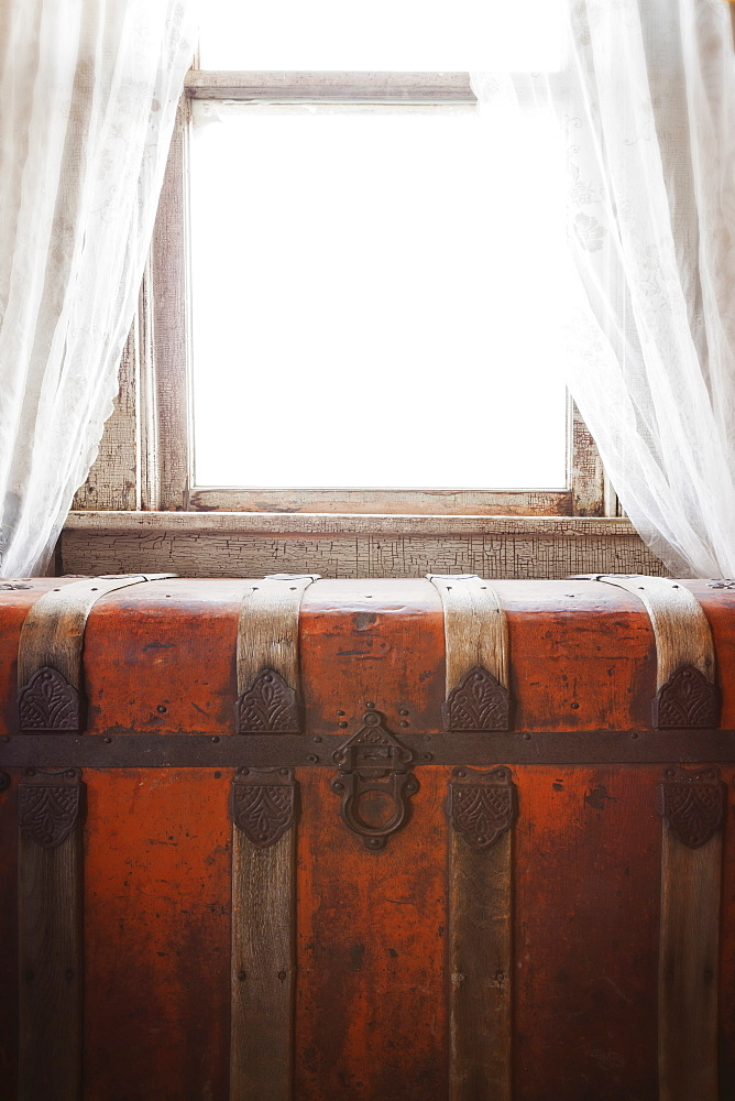 Antique steamer trunk in front of window with curtains