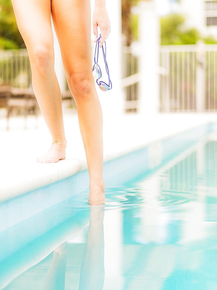 Woman checking water at swimming pool