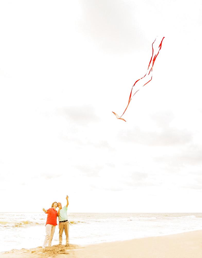 Couple flying kite together on beach, Jupiter, Florida